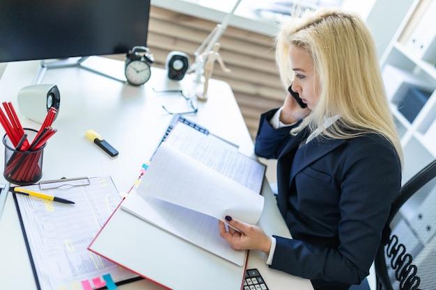 Ragazza che si siede allo scrittorio in ufficio, che parla sul telefono e che esamina i documenti.