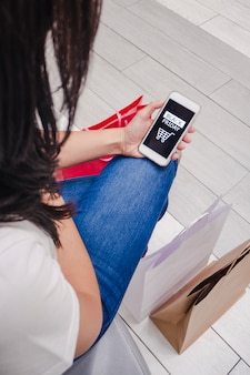 Ragazza che si siede con le borse sul pavimento che guarda sul suo cellulare l'applicazione del black friday