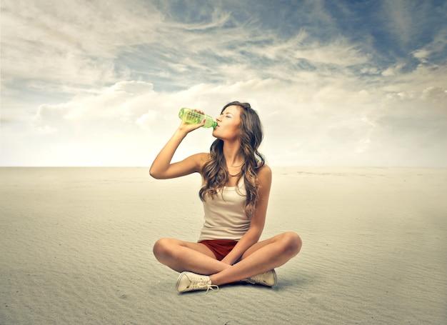Ragazza che si siede e che beve da una bottiglia