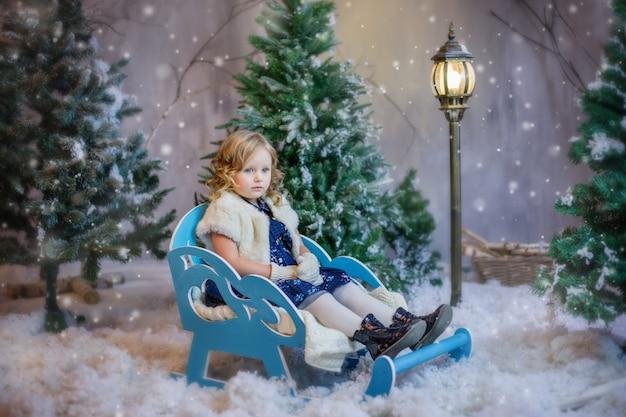 Ragazza che si siede in una slitta nella neve