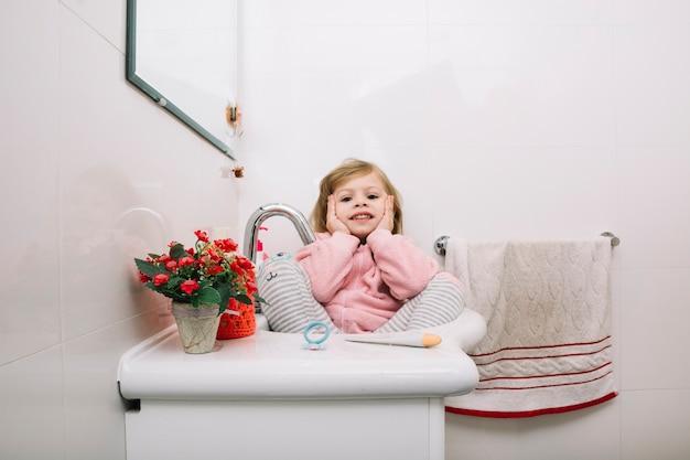 Ragazza che si siede nel lavandino del bagno con vasi di fiori