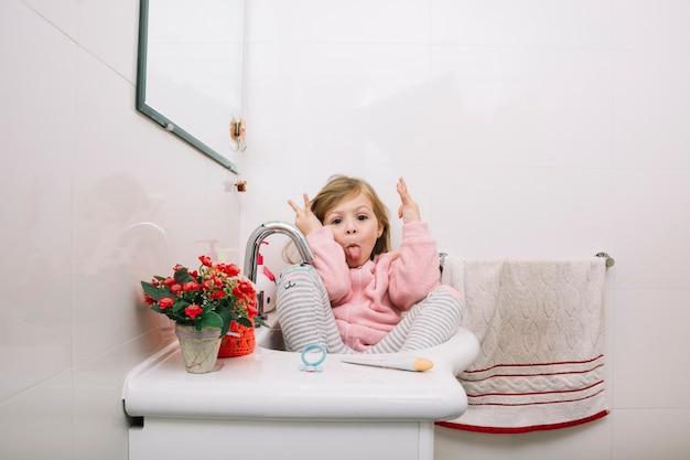 Ragazza che si siede nel lavandino facendo espressione divertente
