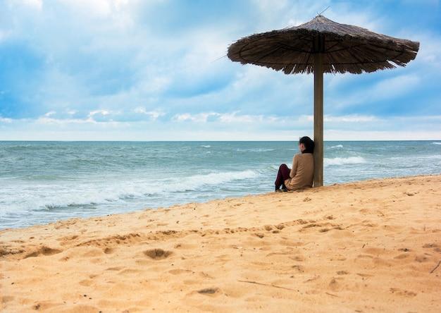 Ragazza che si siede sotto il parasole che osserva lontano i mari