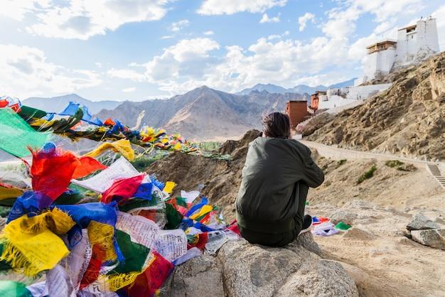 Ragazza che si siede su una roccia che domina la città di leh con i suoi capelli che saltano leh, ladakh, india