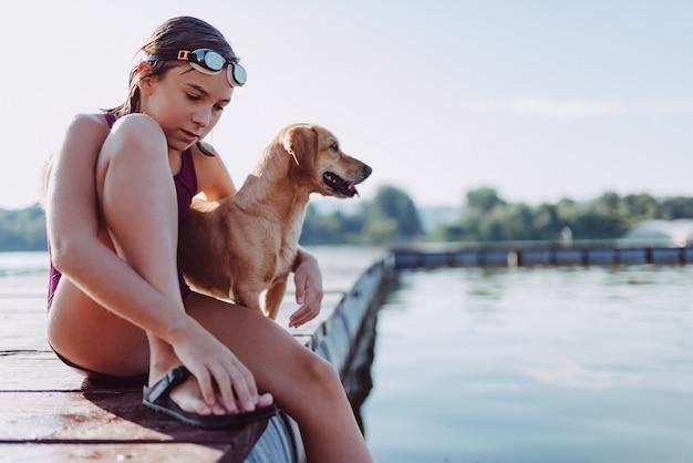 Ragazza che si siede sul bacino del fiume con il suo cane