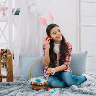 Ragazza che si siede sul letto che ascolta il rumore dall'uovo di pasqua rosso