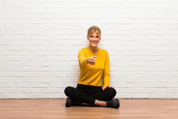Ragazza che si siede sul pavimento che agita le mani per la chiusura del buon affare