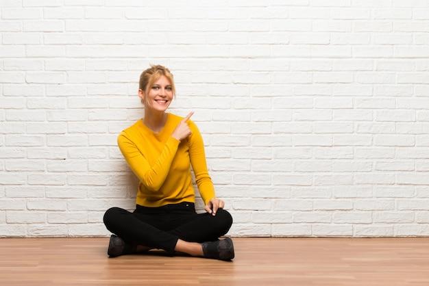 Ragazza che si siede sul pavimento che indica il lato per presentare un prodotto