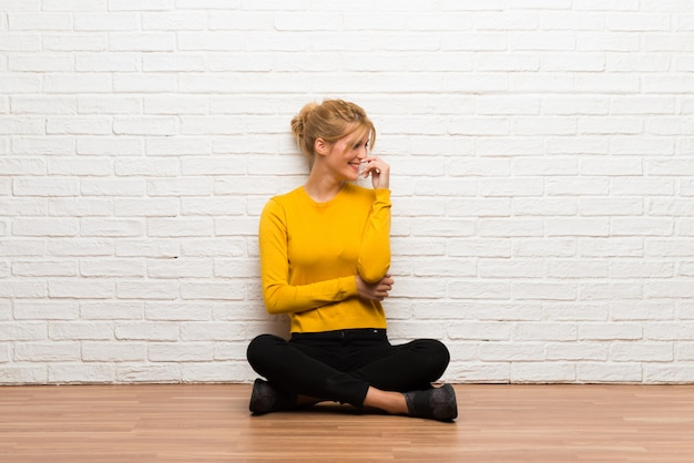 Ragazza che si siede sul pavimento che sorride con un'espressione dolce