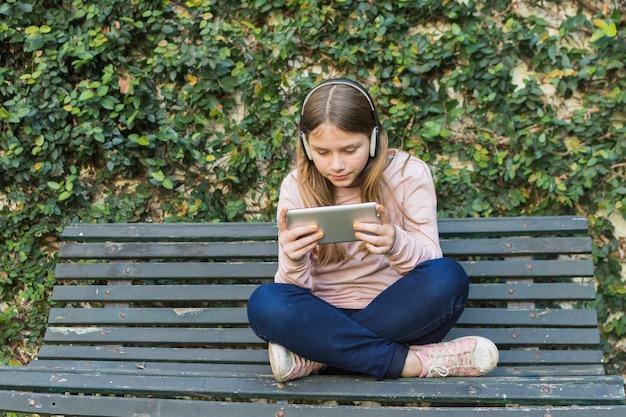 Ragazza che si siede sulla panchina che indossa la cuffia utilizzando il telefono cellulare nel parco
