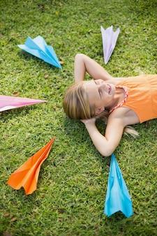 Ragazza che si trova sull'erba intorno agli aerei di carta