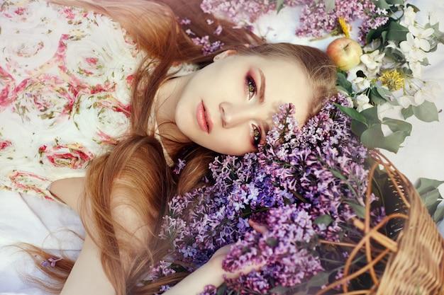 Ragazza che si trova sull'erba nei rami dei fiori lilla