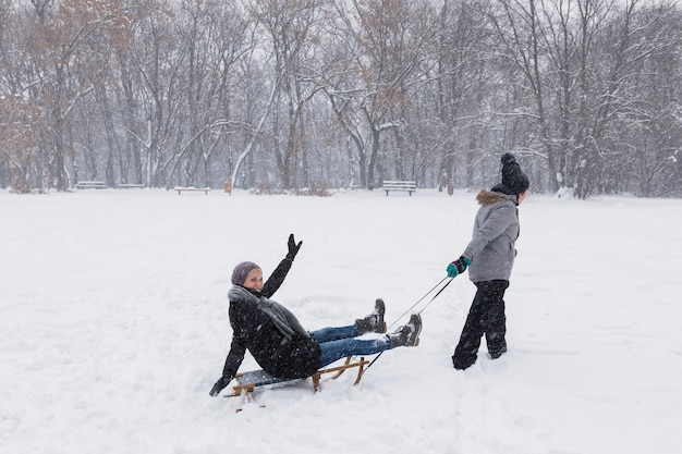 Ragazza che sledding sua madre al winter park