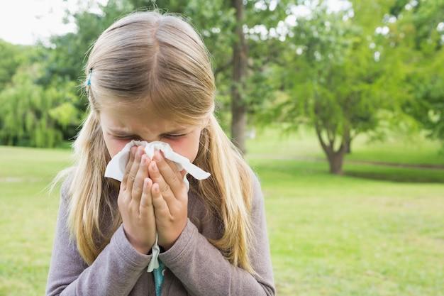 Ragazza che soffia il naso con la carta velina al parco
