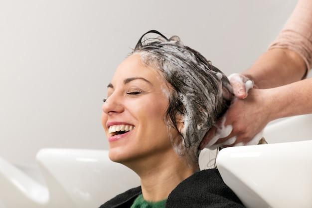 Ragazza che sorride durante i suoi capelli che sono lavati