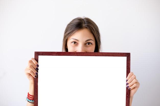 Ragazza che sorride mostrando cartello o manifesto bianco in bianco