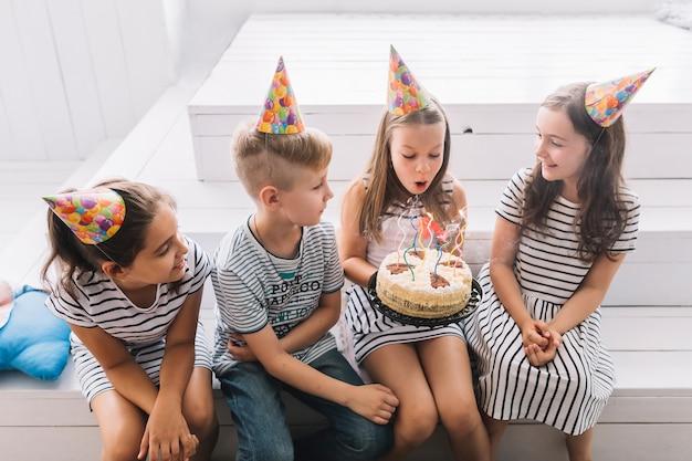 Ragazza che spegne le candele di compleanno in mezzo agli amici