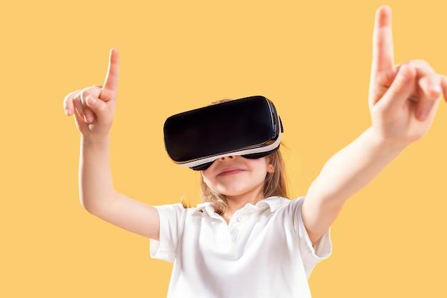 Ragazza che sperimenta il gioco delle cuffie vr. emozioni sorprese sul suo viso. bambino che utilizza un gadget di gioco per la realtà virtuale.