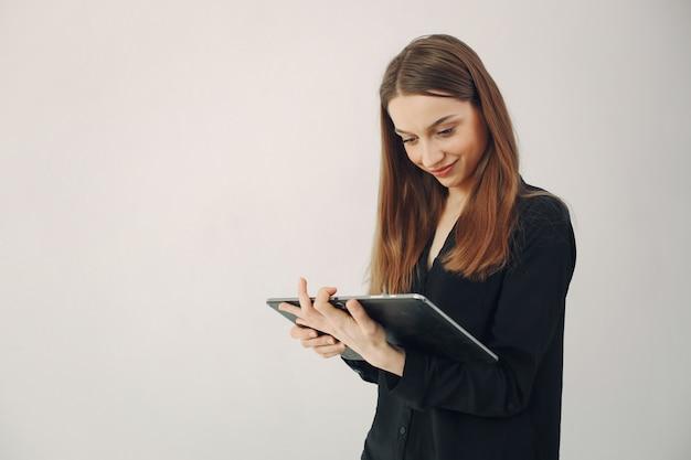 Ragazza che sta su una parete bianca con un computer portatile
