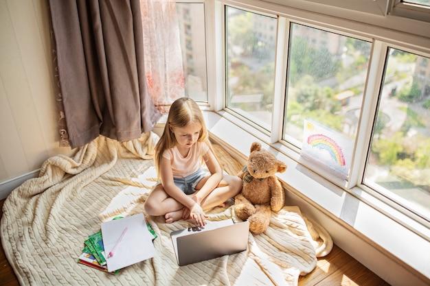 Ragazza che studia i compiti durante la lezione online a casa