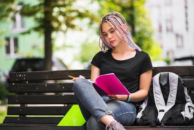 Ragazza che studia sulla panchina nel parco