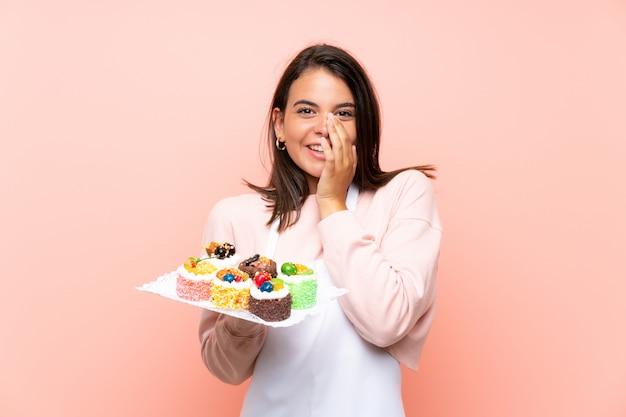 Ragazza che tiene i lotti di mini torte differenti sopra la parete isolata con espressione facciale di sorpresa