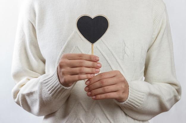 Ragazza che tiene il bordo nero del cuore su bianco