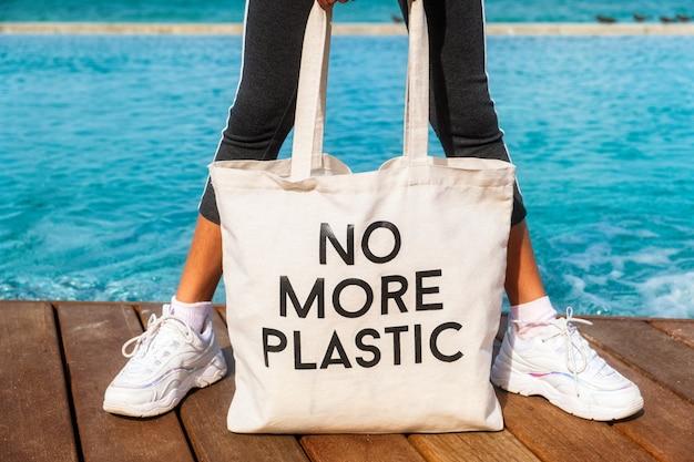 Ragazza che tiene la borsa di eco con sospiro nessuna più plastica sul decking della piscina