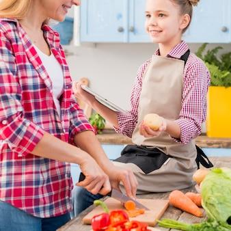 Ragazza che tiene patata e tavoletta digitale in mano guardando sua madre taglio di verdure con coltello