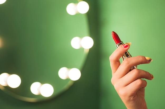 Ragazza che tiene rossetto rosso davanti a uno specchio