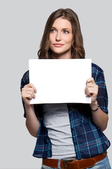 Ragazza che tiene tabellone per le affissioni bianco