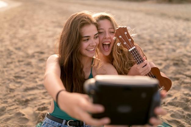 Ragazza che tiene ukulele in mano prendendo autoritratto dalla fotocamera istantanea in spiaggia