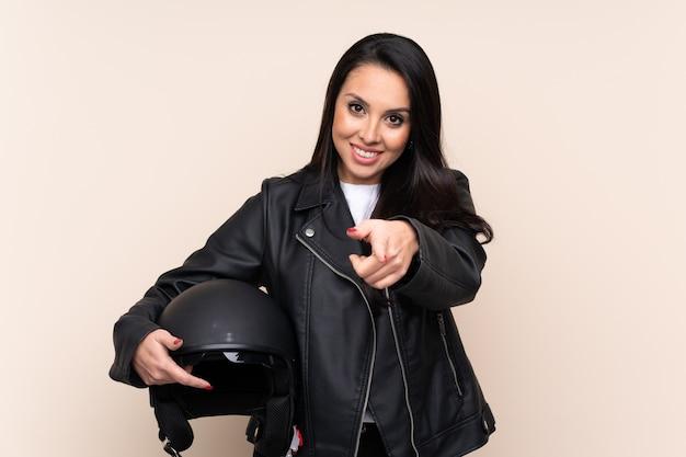 Ragazza che tiene un casco del motociclo sopra il dito dei punti voi