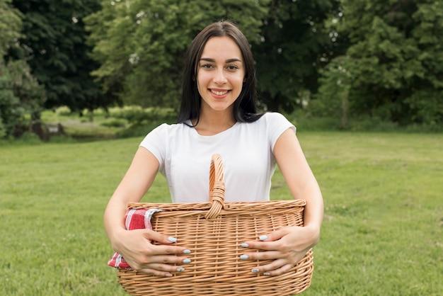 Ragazza che tiene un cestino da picnic