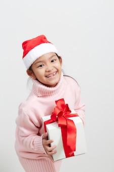 Ragazza che tiene un contenitore di regalo in maglione e cappello di santa