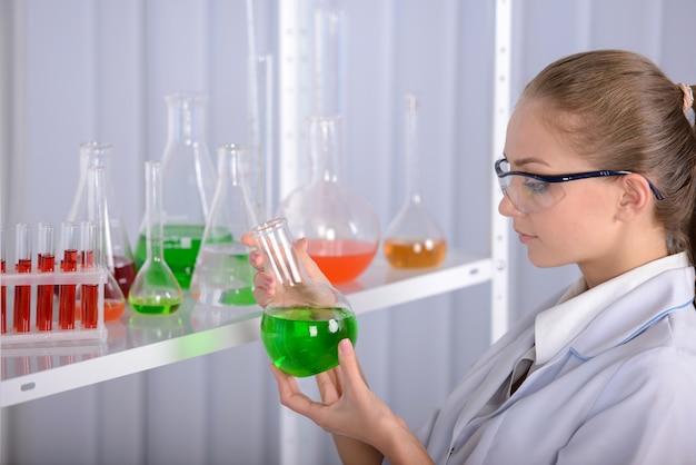 Ragazza che tiene un liquido verde in mani in laboratorio.