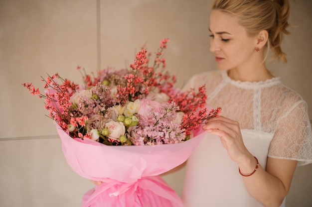 Ragazza che tiene un mazzo della molla di colore rosa tenero e dei fiori bianchi