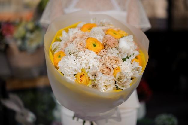 Ragazza che tiene un mazzo delle rose gialle della peonia e del giacinto bianco