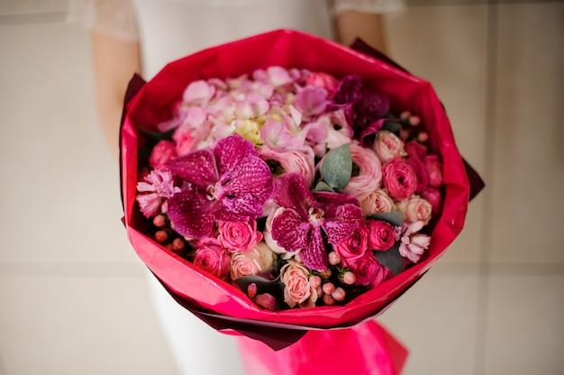 Ragazza che tiene un mazzo di primavera di teneri fiori rosa e cremisi