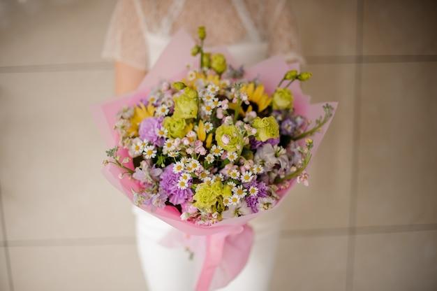 Ragazza che tiene un mazzo di primavera di teneri fiori verdi e viola e piccole camomille