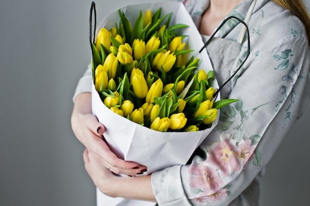 Ragazza che tiene un mazzo di tulipani gialli.
