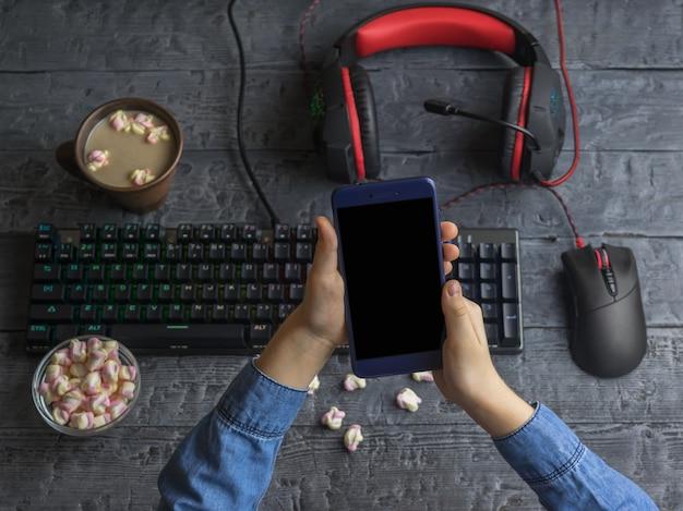 Ragazza che tiene un telefono cellulare sullo sfondo di accessori per computer, caffè e caramelle gommosa e molle