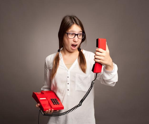 Ragazza che tiene un telefono su fondo grigio