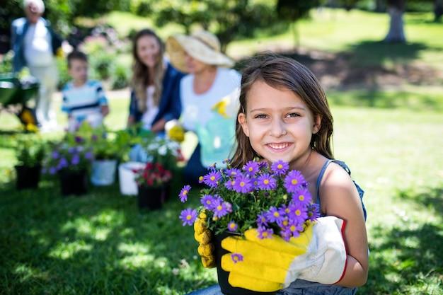 Ragazza che tiene un vaso di fiore mentre facendo il giardinaggio con la famiglia