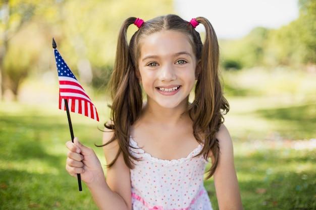 Ragazza che tiene una bandiera americana