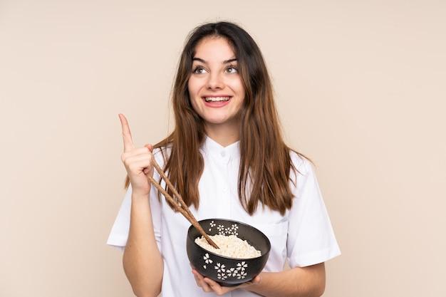 Ragazza che tiene una ciotola piena di noodles sul muro isolato che intende realizzare la soluzione mentre si solleva un dito
