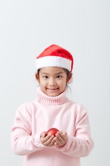 Ragazza che tiene una palla rossa di natale in maglione e cappello di santa