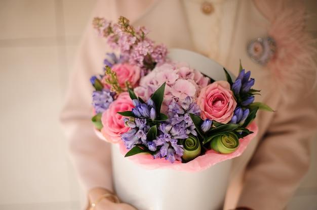 Ragazza che tiene una scatola di primavera di teneri fiori rosa e viola