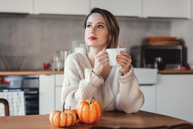 Ragazza che tiene una tazza di caffè e che si siede alla tavola