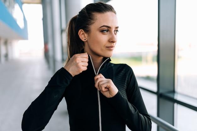 Ragazza che toglie la giacca della tuta sportiva prima dell'allenamento. avvicinamento.
